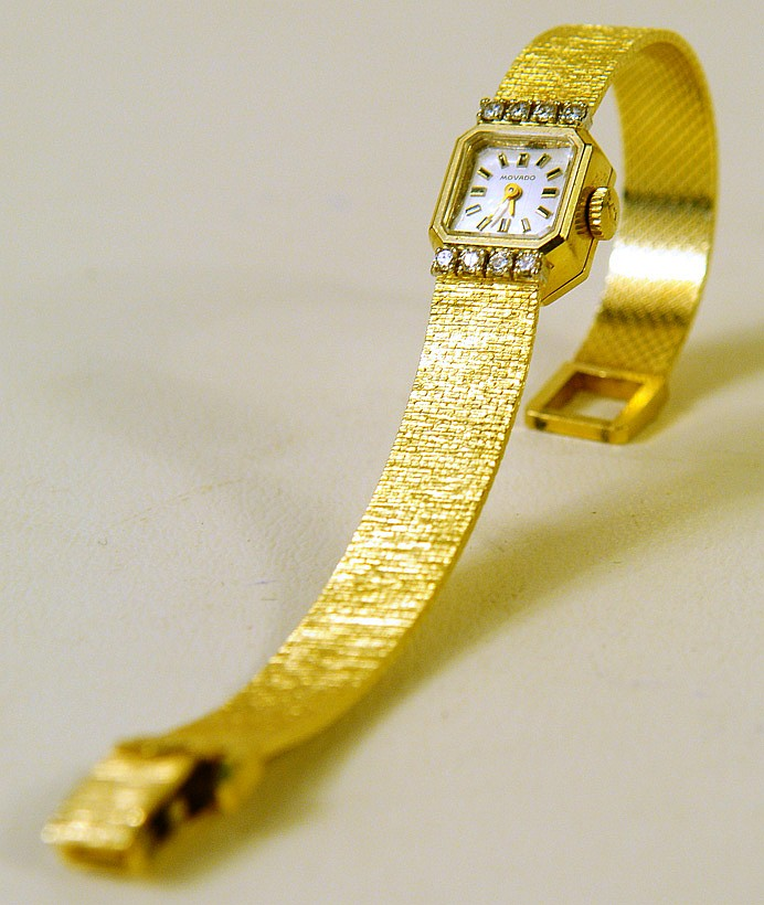 MOVADO 14K GOLD AND DIAMOND LADY'S WRISTWATCH. WIth 14k gold band. Total weight is 24.2 g.