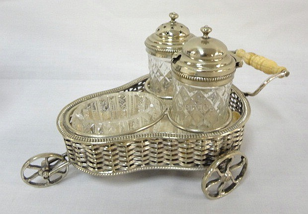 ROLLING CASTOR SET W/2 CUT BOTTLES & A PATTERN GLASS SALT DIP; BONE OR IVORY HANDLE; SILVER PLATED WOVEN HOLDER IS HALLMARKED D & S W/A FLEUR DI LIS TYPE SYMBOL & A CHICKEN; 7 1/2 IN L